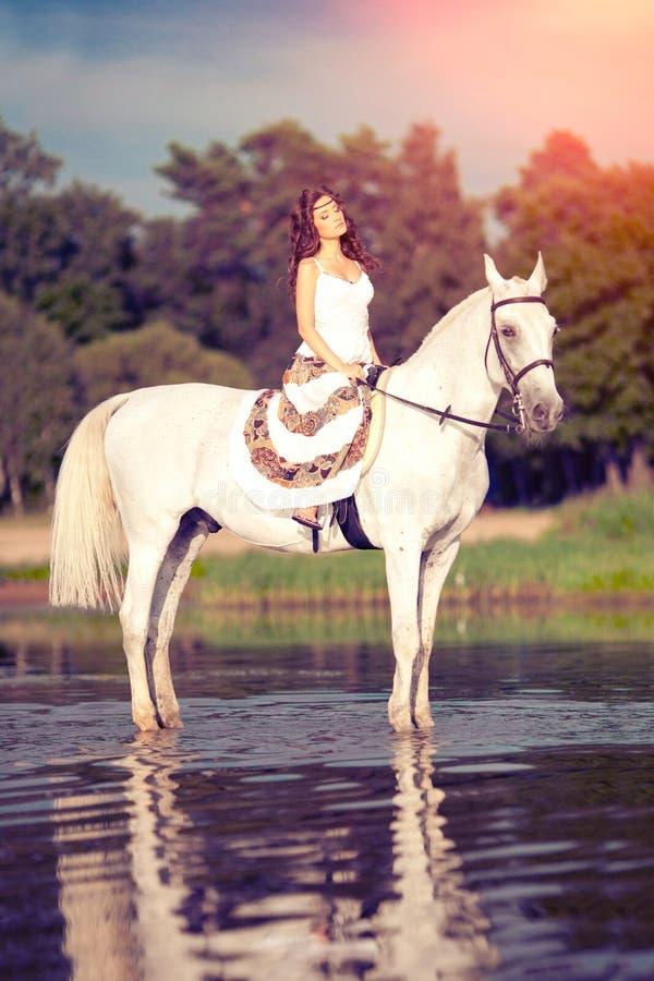 Ung kvinna på en häst Hästryggryttare, kvinnaridninghäst på b royaltyfri foto