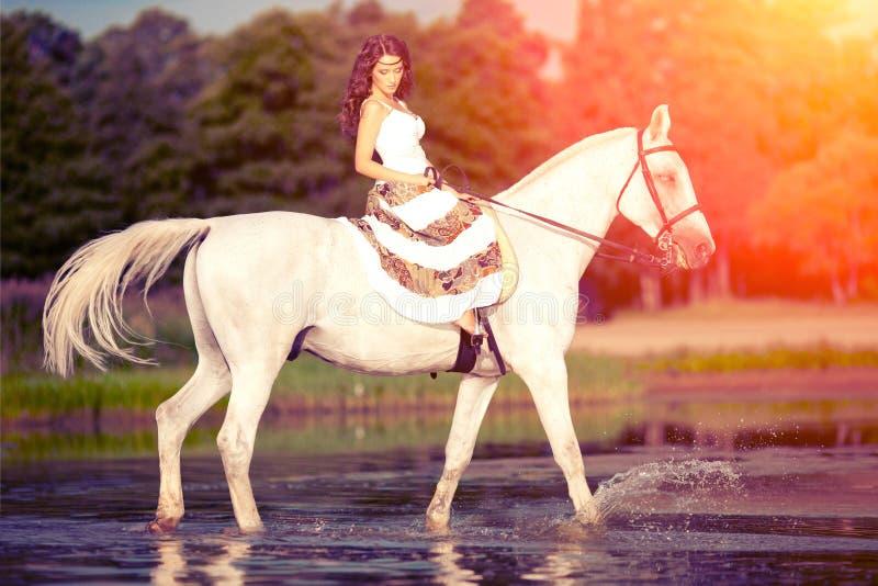 Ung kvinna på en häst Hästryggryttare, kvinnaridninghäst på b arkivbilder