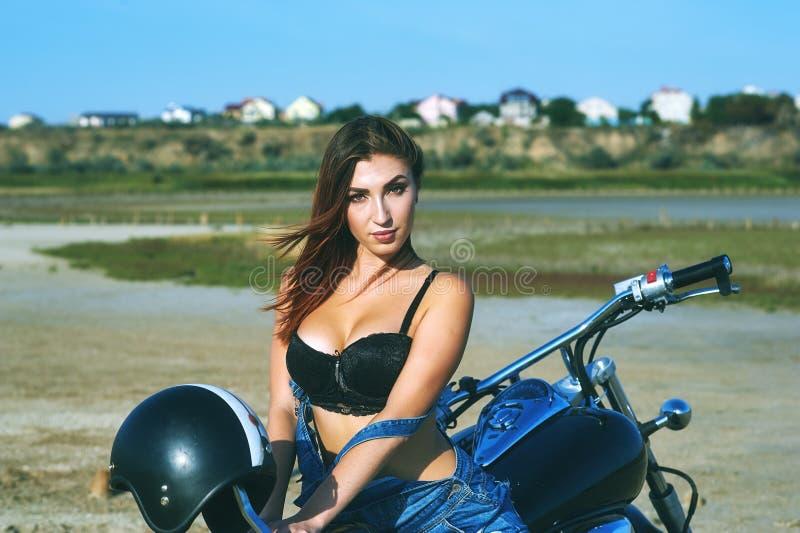 Ung kvinna på en motorcykel på en sommardag royaltyfri foto