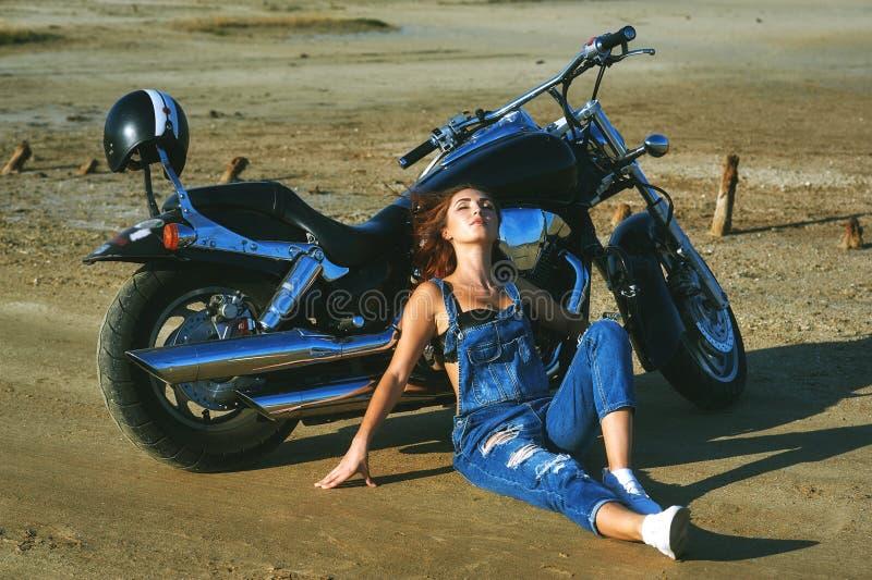 Ung kvinna på en motorcykel på en sommardag arkivfoto