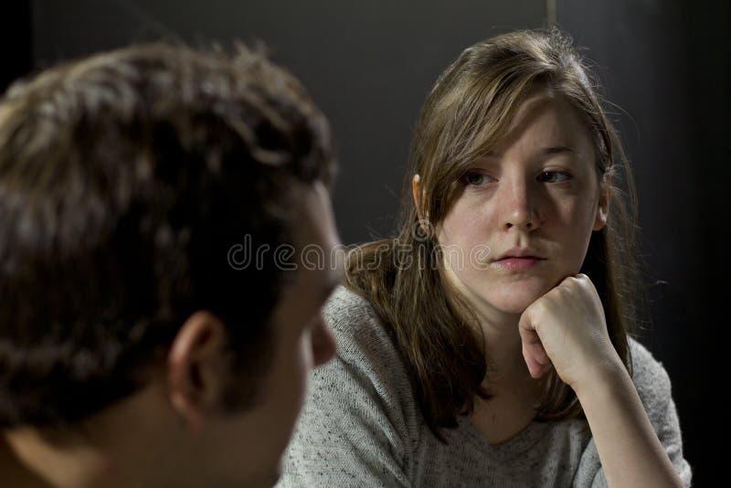 Ung kvinna på en stödgrupp som lyssnar till mans vittnesbörd royaltyfria foton