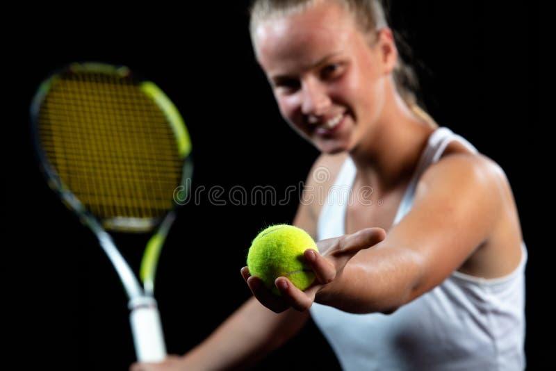 Ung kvinna på en tennisövning Nybörjarespelare som rymmer en racket som lär basfärdigheterer svart stående för bakgrund arkivbilder