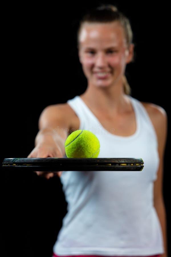 Ung kvinna på en tennisövning Nybörjarespelare som rymmer en racket som lär basfärdigheterer svart stående för bakgrund royaltyfri bild