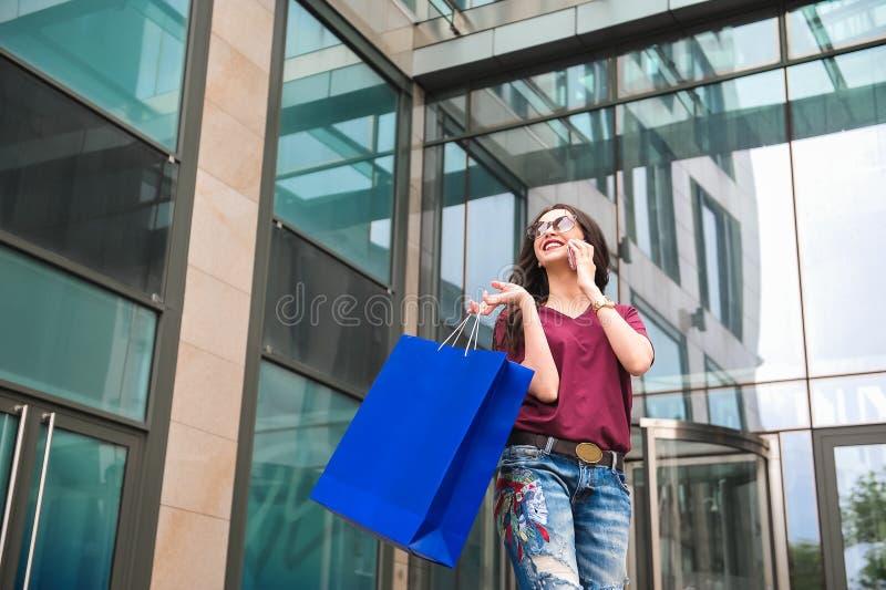 Ung kvinna på gatan med shoppingpåsen som talar på mobiltelefonen arkivfoto
