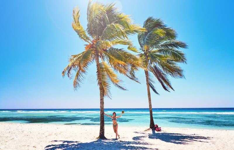 Ung kvinna på gladlynta glade kokosnötpalmträd för strand Karibiskt hav för strand, Kuba arkivfoto