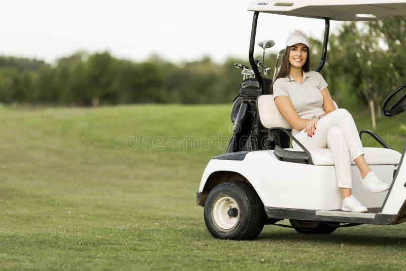 Ung kvinna på golfvagnen royaltyfria foton