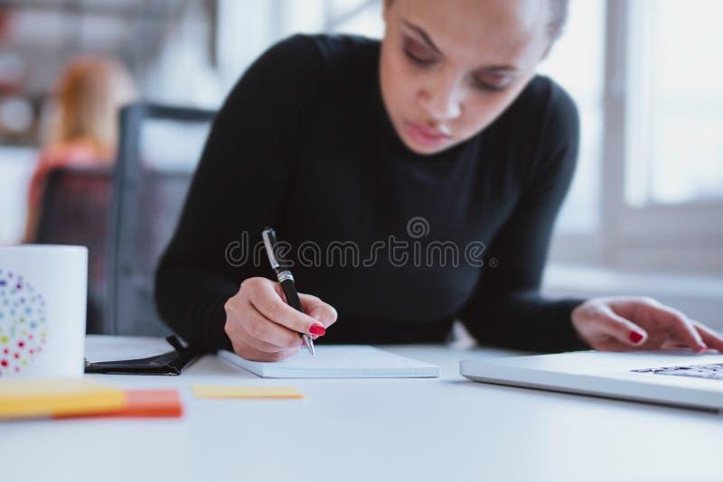 Ung kvinna på hennes skrivbord som tar anmärkningen royaltyfria foton