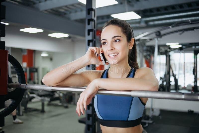 Ung kvinna på idrottshallen genom att använda konditionutrustning royaltyfria bilder