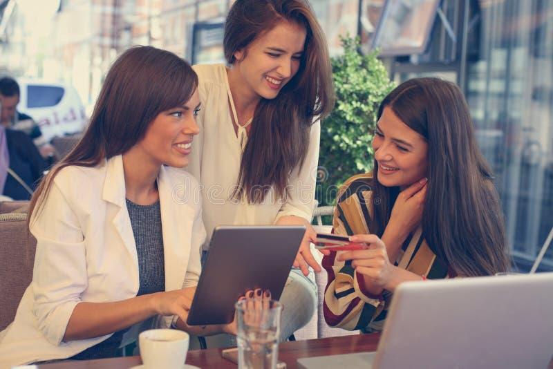 Ung kvinna på kafét som direktanslutet kontrollerar kreditkorten fotografering för bildbyråer