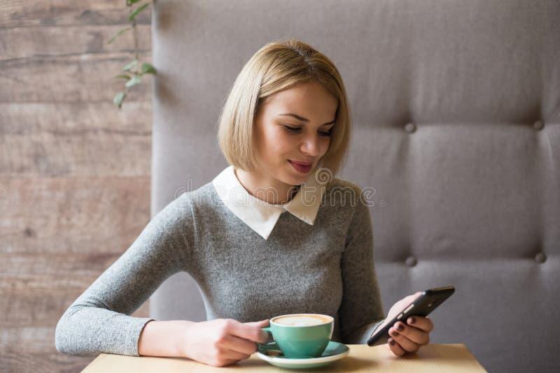 Ung kvinna på kafét som dricker kaffe och använder mobiltelefonen royaltyfri foto