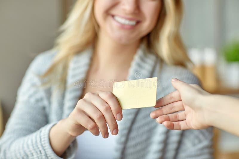 Ung kvinna på kafét som ger en kreditkort i annan hand arkivbild