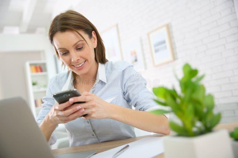 Ung kvinna på kontoret genom att använda hennes smartphone fotografering för bildbyråer