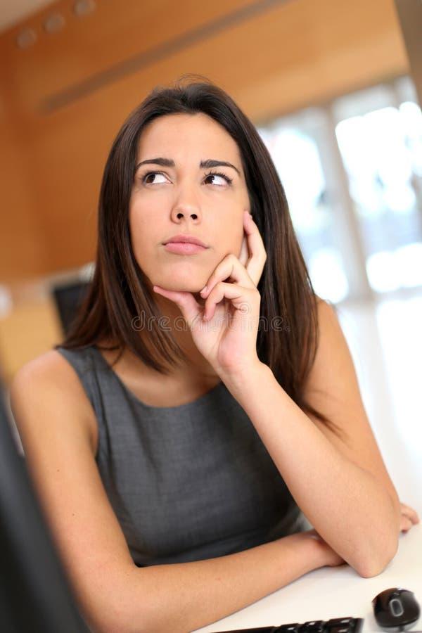 Ung kvinna på kontoret som det är fundersamt arkivbild