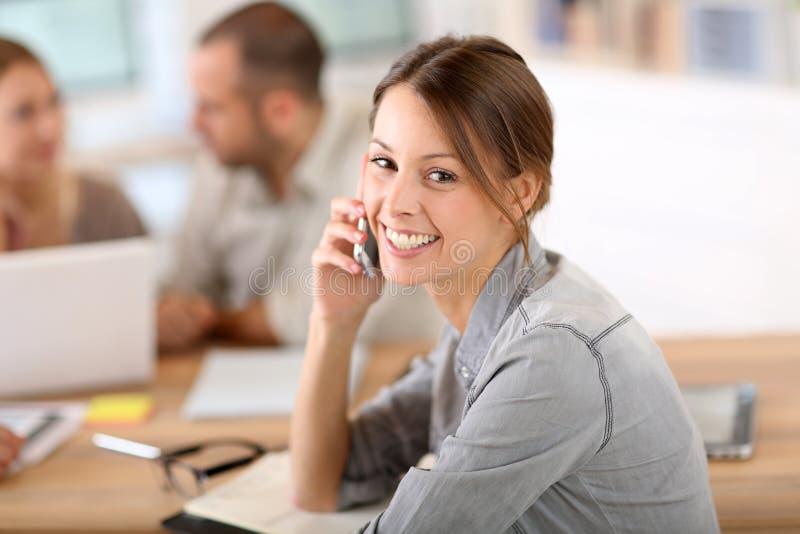 Ung kvinna på kontoret som förhandlar på telefonen royaltyfria bilder