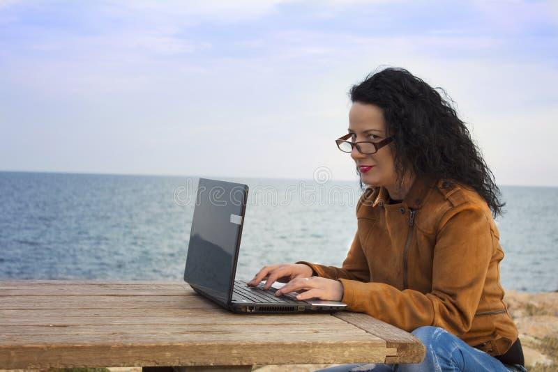 Ung kvinna på kust med datoren fotografering för bildbyråer