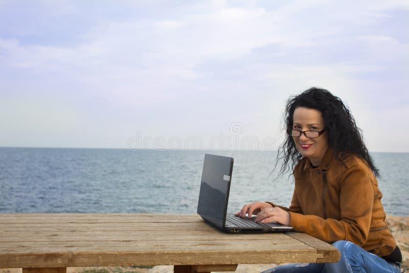 Ung kvinna på kust med datoren 2 fotografering för bildbyråer