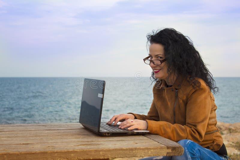 Ung kvinna på kust med datoren 3 royaltyfri foto