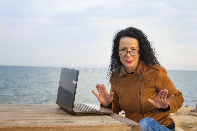 Ung kvinna på kust med datoren 4 royaltyfri bild