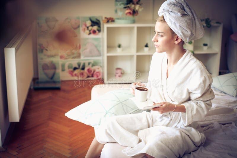 Ung kvinna på morgonen som dricker kaffe på säng royaltyfri bild