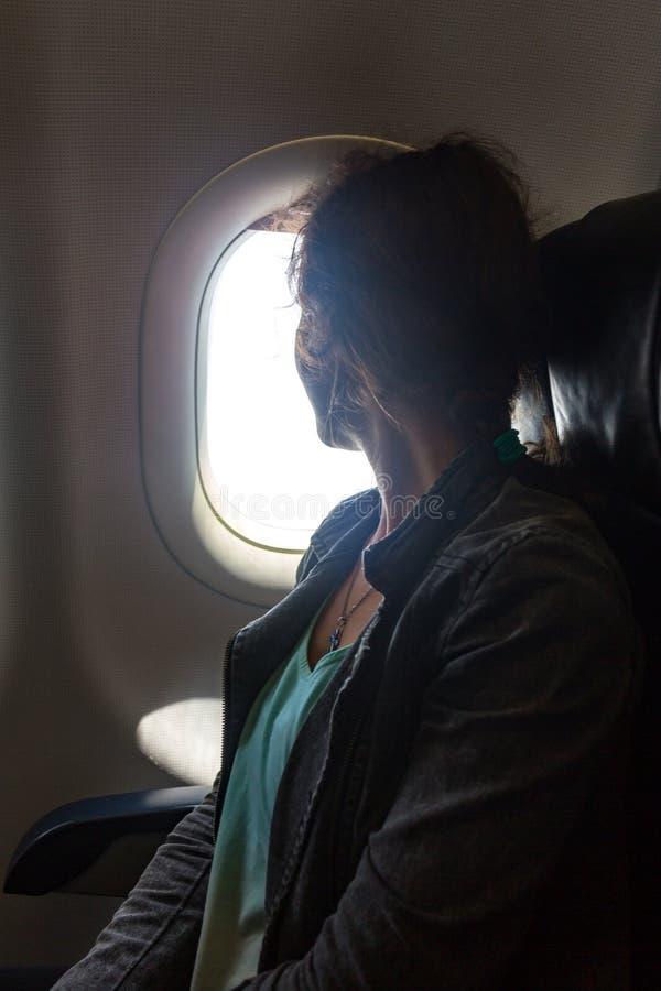 Ung kvinna på passagerareplats nära fönster i flygplan fotografering för bildbyråer
