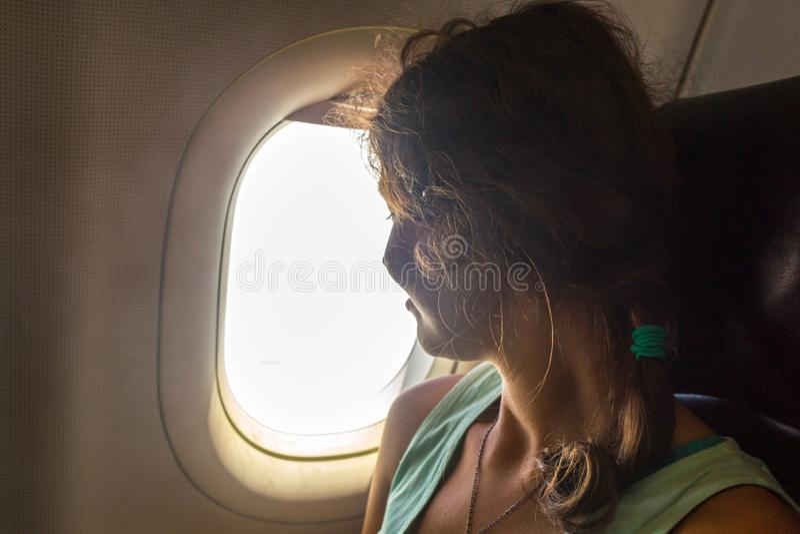 Ung kvinna på passagerareplats nära fönster i flygplan arkivfoto