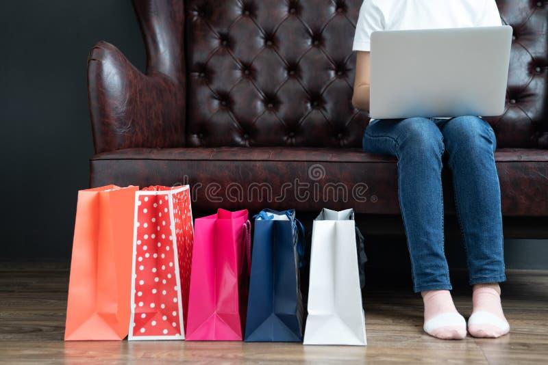 Ung kvinna på soffan som direktanslutet shoppar med bärbara datorn, hållande kreditkort för ung kvinna och använder bärbar datord arkivbild