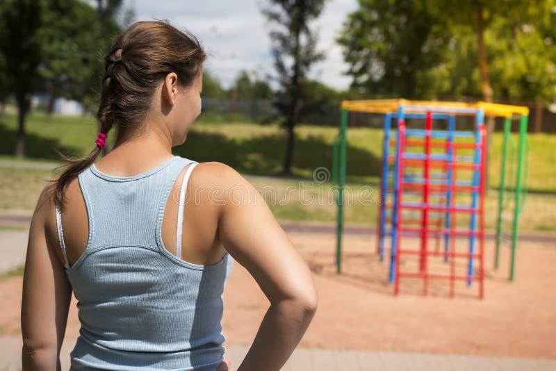Ung kvinna på sportlekplats på ljus sommardag Flickan går att spela sportar och kondition fotografering för bildbyråer