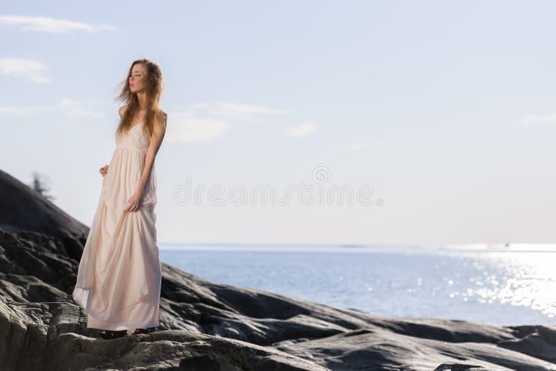 Ung kvinna på stenig kust arkivfoto