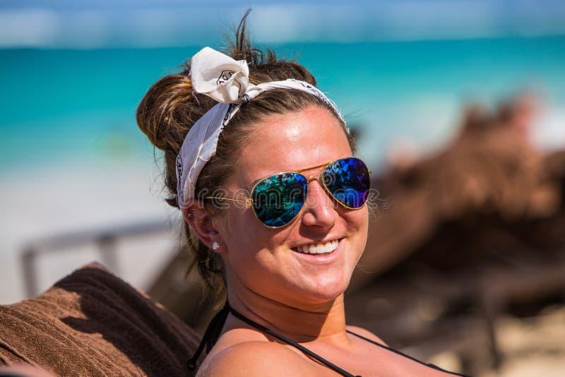 Ung kvinna på stranden i solglasögon arkivbilder
