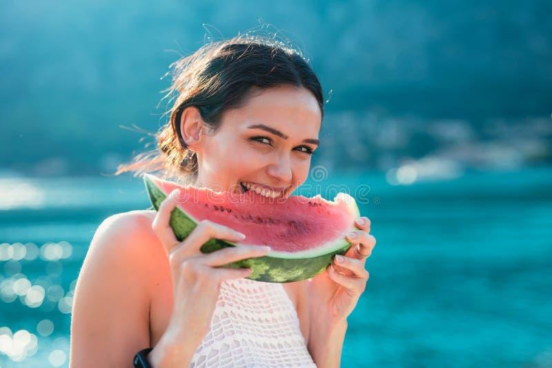 Ung kvinna på stranden som äter vattenmelon royaltyfri bild
