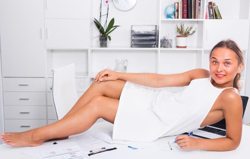 Ung kvinna på tabellen på kontoret arkivfoto