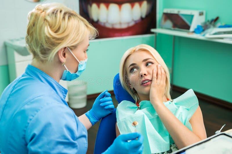 Ung kvinna på tandläkaren som klagar om en tandvärk dentistry Doktor och patienten royaltyfria foton