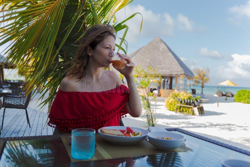 Ung kvinna p? ferie i en tropisk ? som ?ter en sund frukost royaltyfria bilder