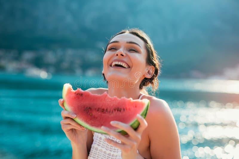 Ung kvinna p? stranden som ?ter vattenmelon royaltyfria bilder