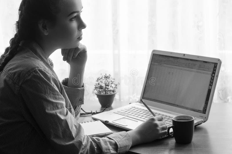 Ung kvinna som är borttappad i tanke som sitter på en bärbar dator, svartvit bild royaltyfri fotografi