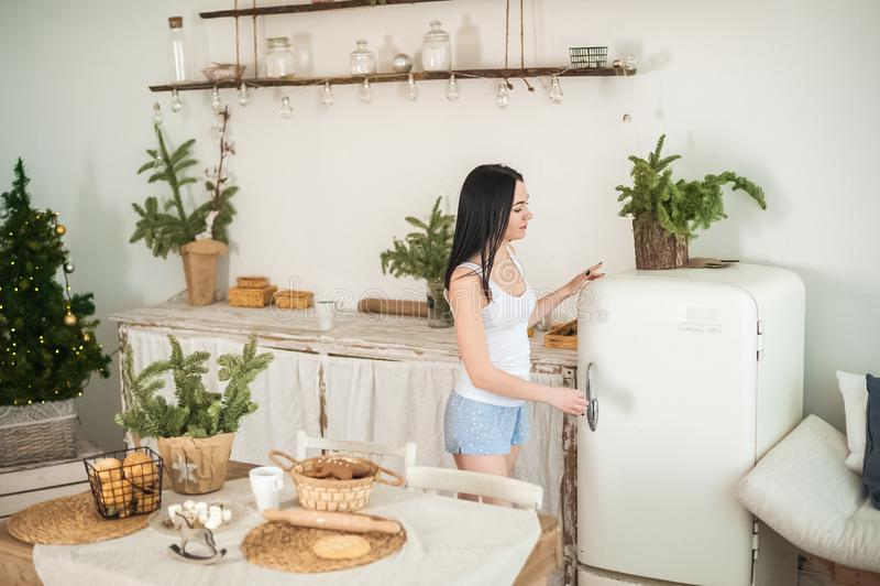 Ung kvinna som är hemmastadd i morgonen i köket i ljusa färger Flickan äter kakor, öppnar kylskåpet, förbereder ingefäran royaltyfri foto
