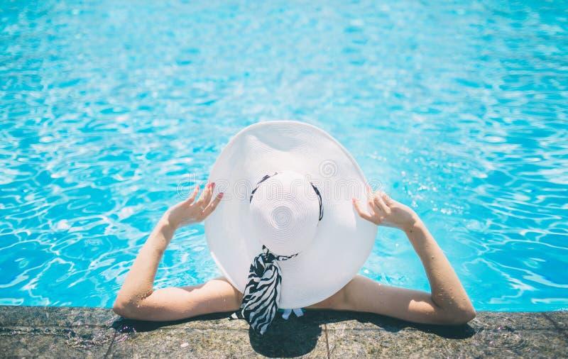 Ung kvinna som är lycklig i den stora hatten som kopplar av på simbassängen, lopp nära stranden i solnedgången begreppssommar arkivfoto