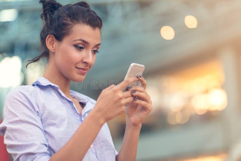 Ung kvinna som är upptagen med att kalla och att prata på ståenden för mobiltelefonsidosikt arkivfoto