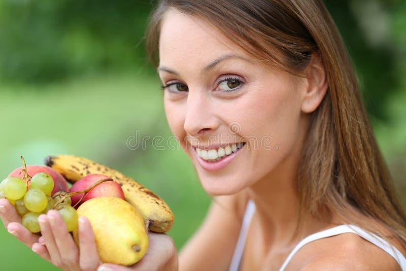 Ung kvinna som är utomhus- med frukter i händer arkivfoton