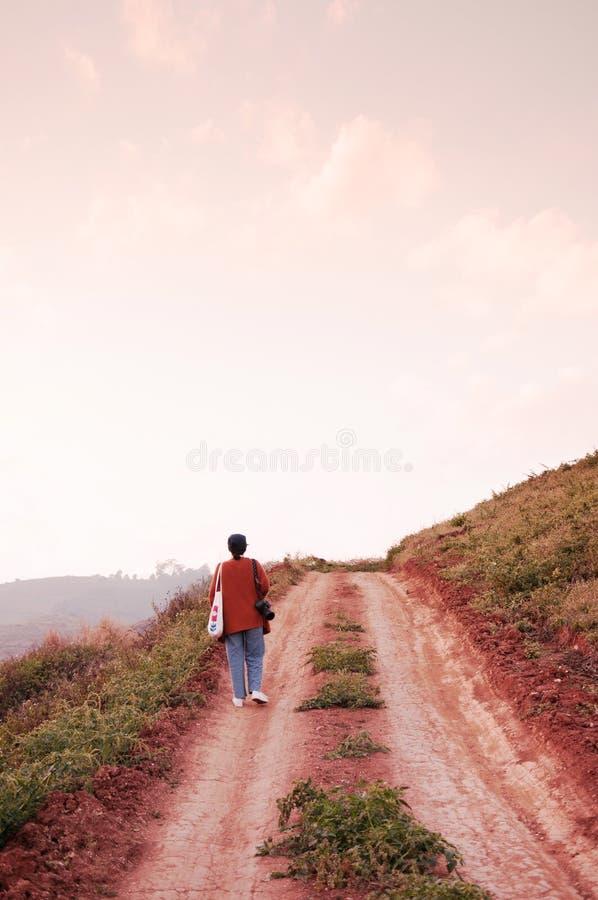 Ung kvinna som är walkin på vägen för smutsbanaland på kullen på även royaltyfri foto
