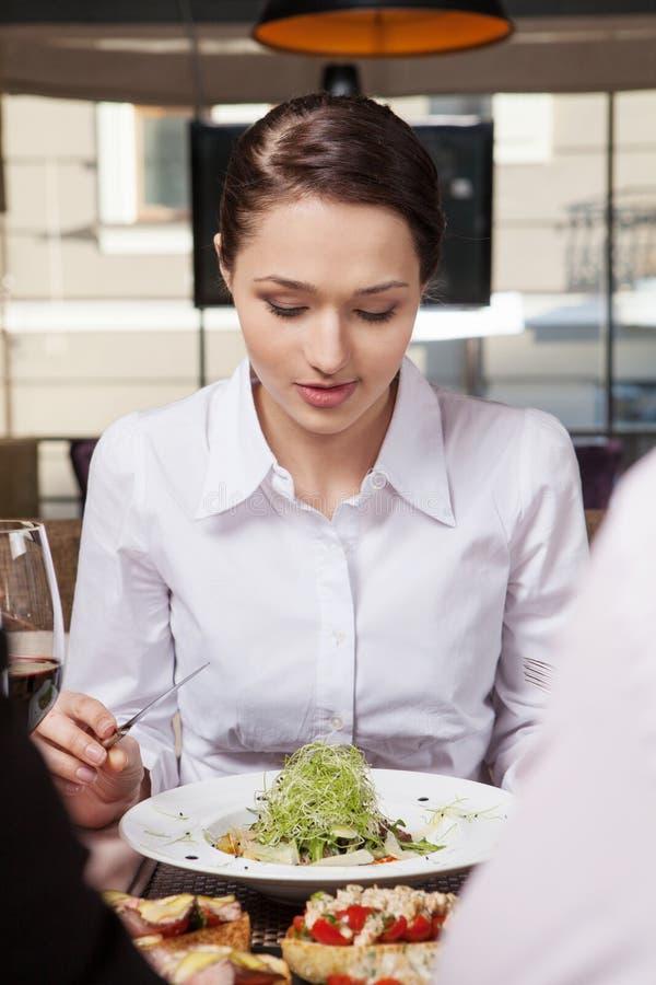Ung kvinna som äter blandad grönsaksallad i kafé Kvinna som äter sund salladlunch i kafé med vänner arkivfoto