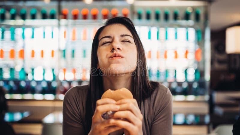 Ung kvinna som äter den fettiga hamburgaren Begärsnabbmat Tycka om skyldigt nöje som äter skräpmat Tillfredsställt uttryck avbrot arkivbilder