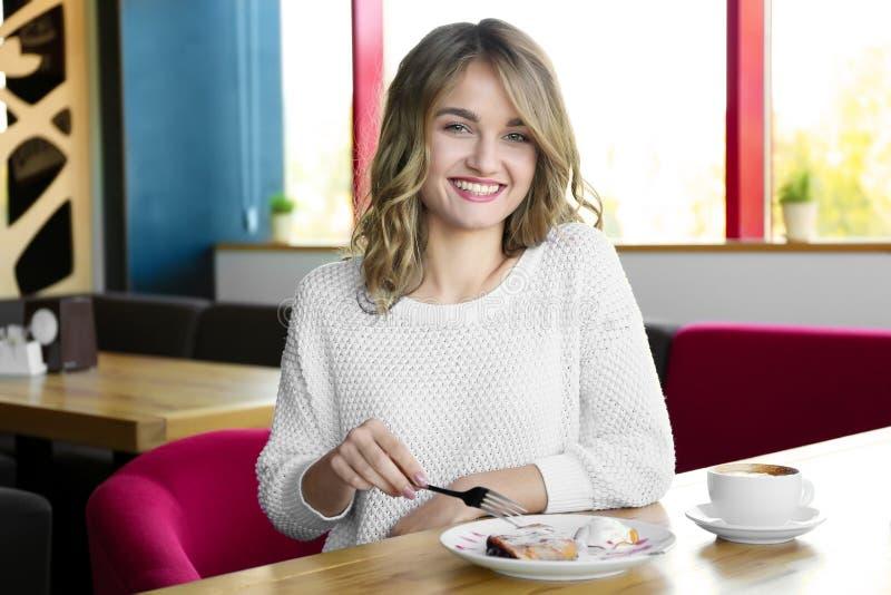 Ung kvinna som äter den läckra efterrätten royaltyfri foto