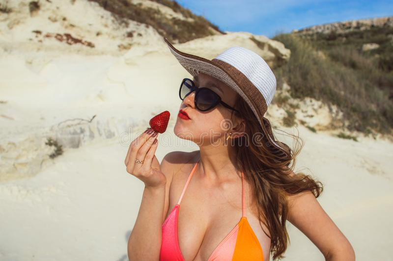Ung kvinna som äter den röda jordgubben arkivbild