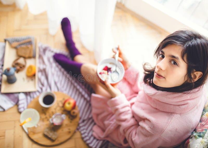 Ung kvinna som äter den sunda frukosten royaltyfria foton
