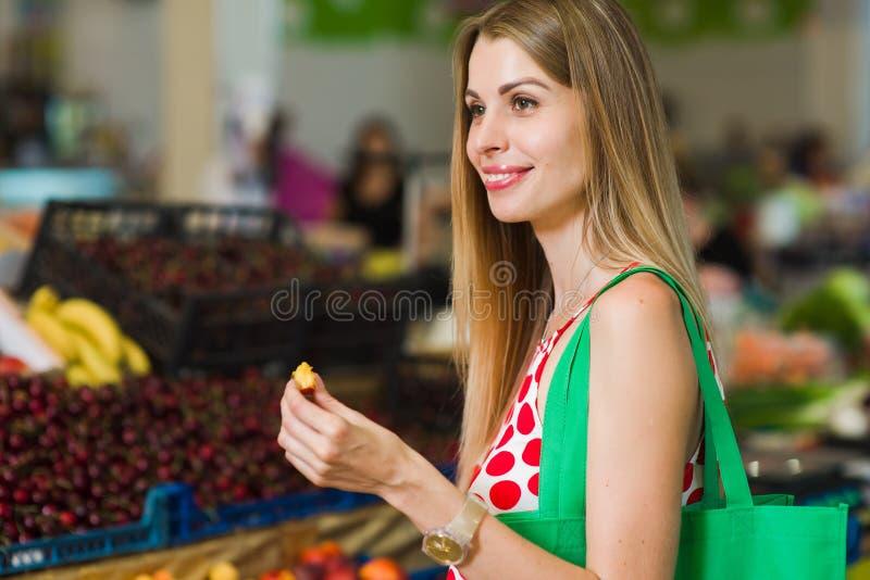 Ung kvinna som äter en persika arkivfoton