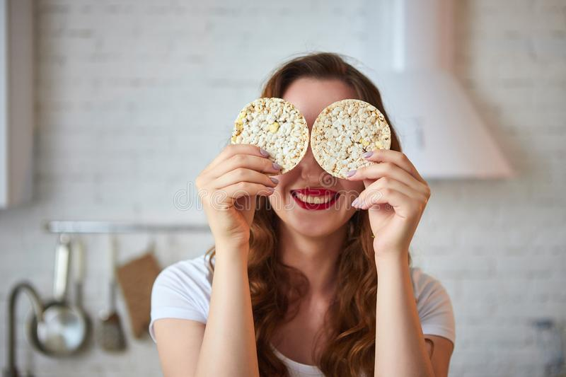 Ung kvinna som äter knaprigt bröd för rågsmällare i köket Sund livsstil H?lsa sk?nhet, bantar begrepp arkivfoton