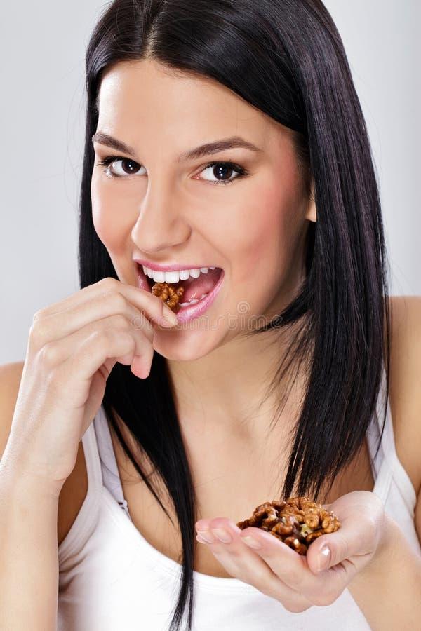 Ung kvinna som äter muttern arkivfoto