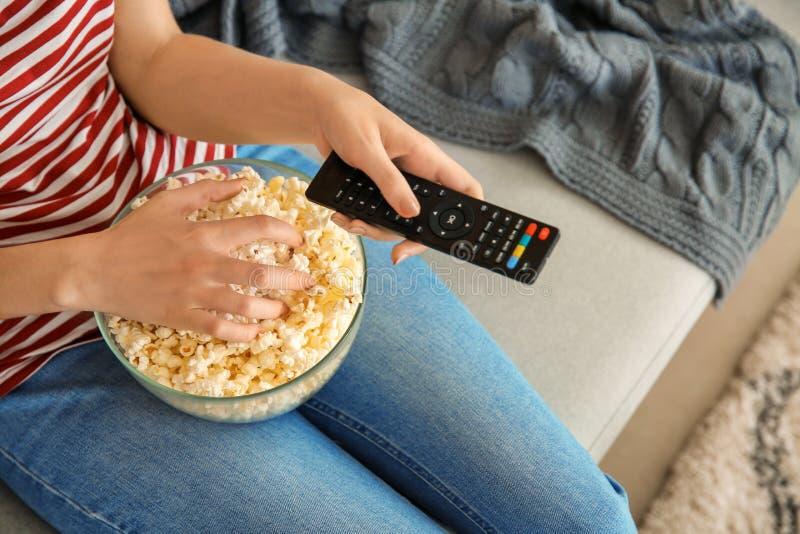 Ung kvinna som äter popcorn, medan hålla ögonen på TV hemma, closeup royaltyfri bild
