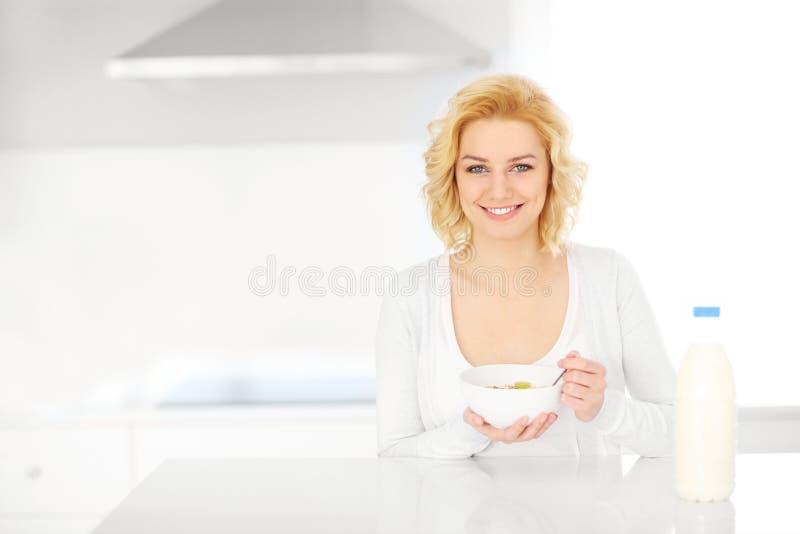 Ung kvinna som äter sädesslag i köket arkivfoton